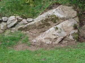 Ein Findling im Steingarten sollte so in das Erdreich eingelassen werden, dass dieser natürlich wirkt.
